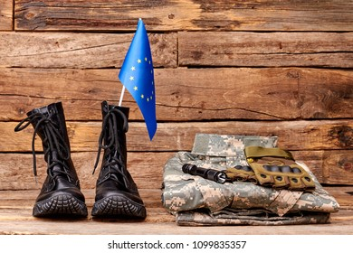 Set of military outfit of european union soldier. Brown wooden desk surface background.