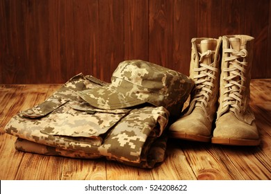 Set of military uniform on wooden background, close up view