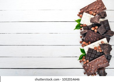A set of milk chocolate and black chocolate hazelnuts. On a white wooden background. Copy space for text.
