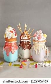 Set of Milk Monster Shakes or Freak Shake. Big Crazy Milkshake or Freakshake with Treats and Sweets Mix. Sweet Drink Dessert Collection in Mason Jars