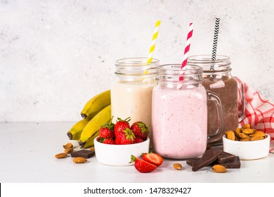 Set of milkshake in mason jars. Banana, chocolate and strawberry milkshakes. Summer dessert. Healthy food.