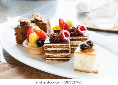 Set of mini cakes in assortment on white plate. Restaurant menu. Chocolate cake with raspberries. Tartlet with fruits. Close up.