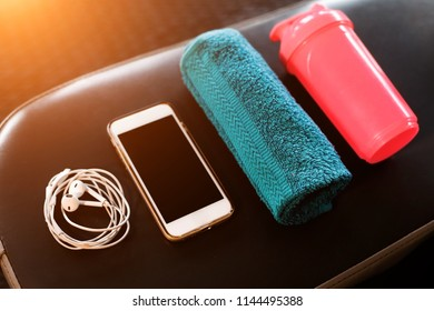 set of mobile phone, earphones, blue towel and a pink shaker lying on a black leather bench in a fitness center. sport equipment and gadgets concept
