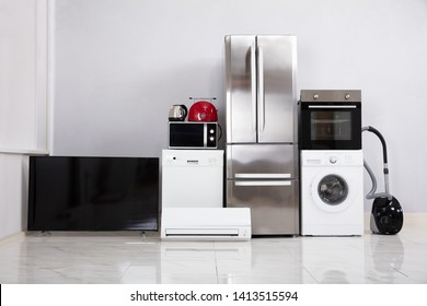 Set Of Modern Appliances On Reflective White Floor In The New Kitchen Apartment