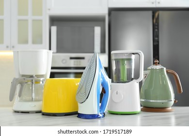 Set of modern home appliances on white marble table in kitchen