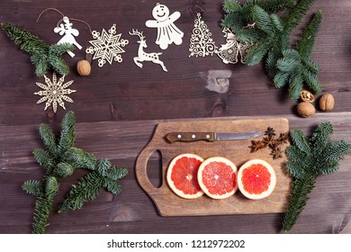the Set for mulled wine: sliced grapefruit with anise on the board on the wooden brown background.