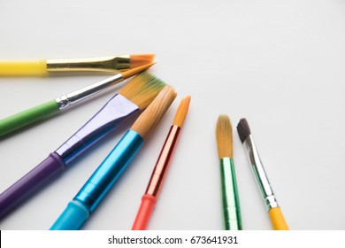 A set of multi-colored brushes of different shapes and textures for drawing with watercolor, gouache and oil with a box for an inscription or logo