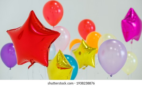 Set of multicolored helium balloons of various colors floating against gray background during holiday celebration