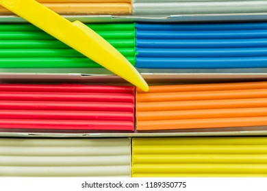 Set of multicolored plasticine bars for modeling in paper box. Top view, eduction and creativity concept