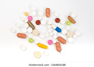 set of multi-colored tablets and capsules on a white background - Image
