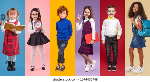 Reihe von multiethnischen, fröhlichen Mädchen und Jungen in stilvollen, lockeren Kleidern, mit Schulmaterial, das auf buntem Hintergrund im Studio lächelt