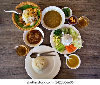 A set of myanmar dish on the wooden table. Dishes are Myanmar(Burmese) style noodle (MonHinGa), Myanmar chicken curry and shrimp paste with soup