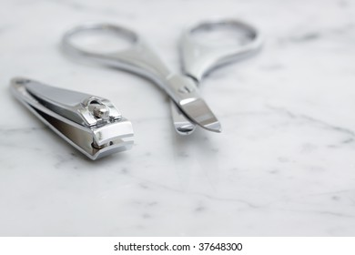 A set of nail scissors & clippers on a marble bench top.