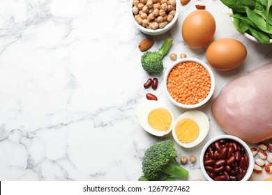 Set of natural food high in protein and space for text on marble background, top view