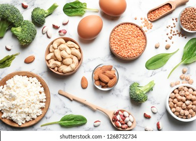 Set of natural food high in protein on marble background, top view