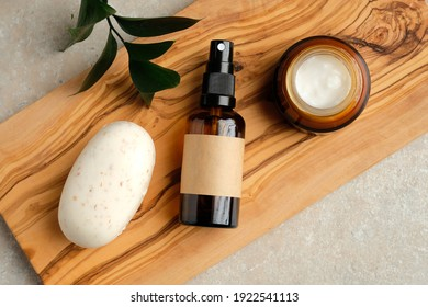 Set of natural organic SPA beauty products on wooden board. Homemade soap, moisturizer cream jar, amber glass spray bottle, green leaf on wooden board.