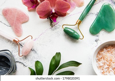Set of natural organic SPA cosmetic with orchid flowers. Flat lay bath salt, face rollers, orchid flowers on marble background. Skin care, beauty treatment concept