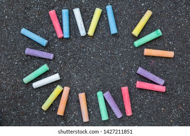 Set of new colorful chalks isolated on grey pavement of sidewalk background. Border or frame made with chalks laying on grey background. Horizontal color photography.