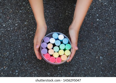 Set of new colorful chalks isolated on grey pavement of sidewalk background. Child ready to make drawings outdoors. Horizontal color photography.