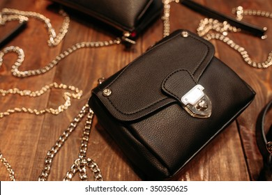 Set of new stylish women's leather handbags.Top view. Several different bags on the wooden background