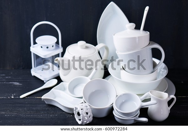 Set of new white dishes with teapot, tea cups, and plates on a black wooden table
