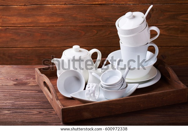 Set of new white dishes with teapot, tea cups, and plates on wooden tray at a wooden table