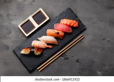 Set of nigiri sushi served on plate on grey background