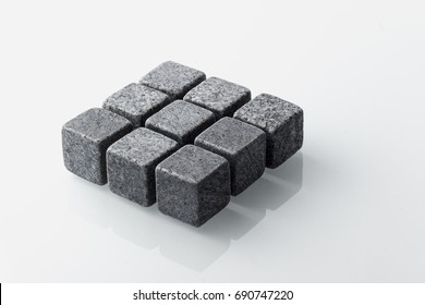 Set of nine spirit chilling stones. Soapstone rocks are carved in cubes to be used as drink chiller (whisky, bourbon ...) Various type of raw minerals produces different colors, such as dark grey.