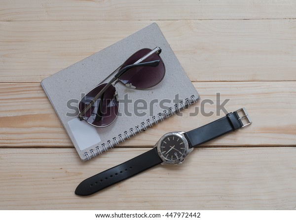 set of notepad, watches, glasses on wooden table.