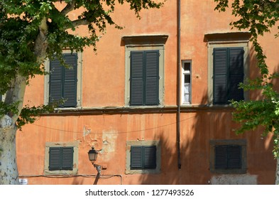 A set of ochre-coloured apartments, in Venice, Italy. The windows have black shutters, and the paint is peeling. A black lamp is attached to the wall, and trees with green leaves frame the view.