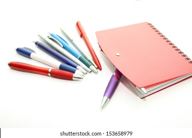 Set of office pens and red notebook on a white background