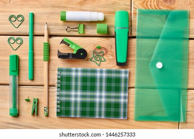 Set of office supplies on wooden background. Paper notebook, folder, pencils, markers, stick glue and other items for education.