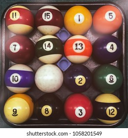A set of old billiard pool game balls in a rack, with chalk.