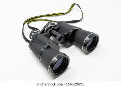 A set of old binoculars set against a white background