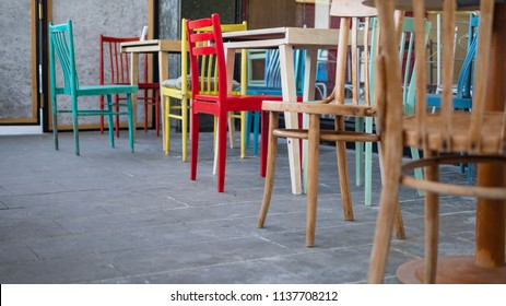 Set of old colorful chairs around tables in a small indie cafe