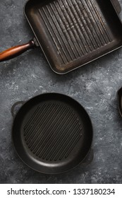 Set of old grill pans on dark stone background top view