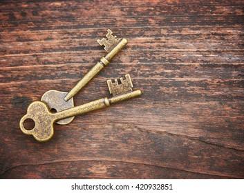 a set of old skeleton keys on a wooden background toned with a retro vintage filter instagram app or action effect