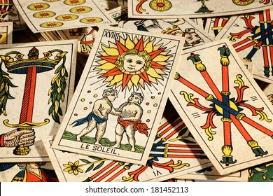Set of old tarot cards lying in a scattered heap with their designs uppermost and a picture of the sun on top