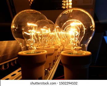 Set of old tungsten bulbs glowing in the dark - energy inefficient
