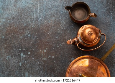 Set of old vintage copper empty tableware on rustic concrete background. Antique copper utensils: pan, teapot, sauce boat. Top view of beautiful aged retro brass cookware from flea market, copy space