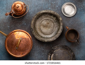 Set of old vintage copper and nickel silver empty tableware on rustic concrete background. Antique utensils: pan, plates, bowls, teapot. Top view of beautiful aged retro cookware from flea market