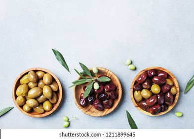 Set from olives in wooden bowls decorated with fresh olive tree branch top view.