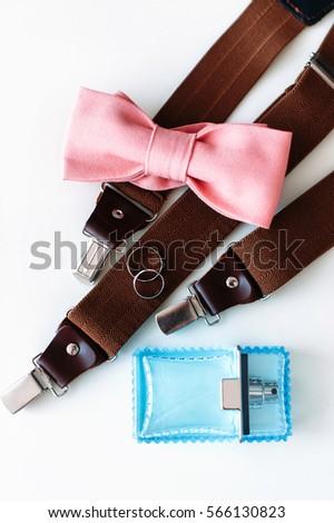 d781492a90fe Set on groom accessories. Wedding rings, pink bow tie, perfume bottle, brown