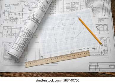 A set of open and rolled up blueprints on wooden table background with a pencil and a ruler lying beside. Engineering and design. Construction projects. Planning.