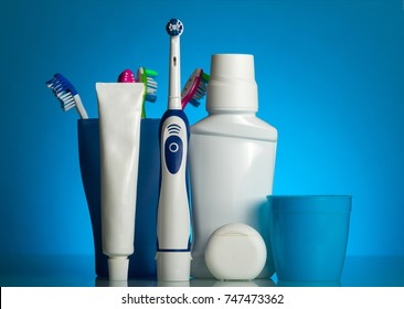A set of oral care products and various toothbrushes on glass shelf