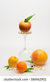 set of orange, apple with drops, lemon, grapefruit and wineglass with pills and capsule isolated on white background, side view