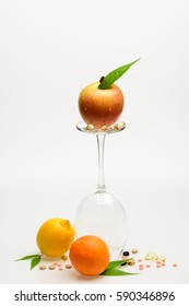 set of orange, apple with drops, lemon and wineglass with pills and capsule isolated on white background, side view