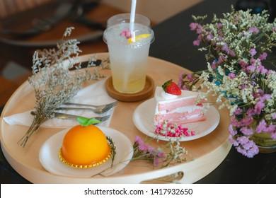 Set of orange cake, strawberry cake, soda water on circle wood tray. Side view
