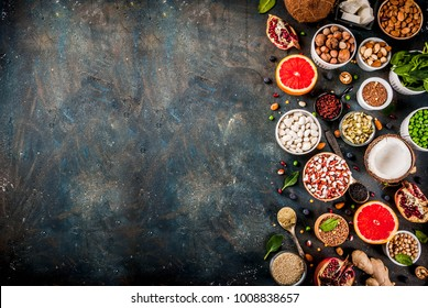 Set of organic healthy diet food, superfoods - beans, legumes, nuts, seeds, greens, fruit and vegetables. Dark blue background copy space top view