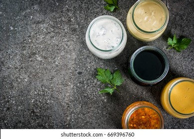Set of organic healthy dietary dressings for salad: sauce vinaigrette, mustard, mayonnaise with spices or ranch, balsamic or soy, basil with yogurt. On a dark stone table. Top view copy space